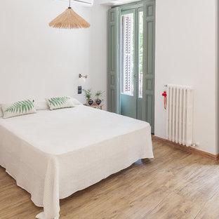 Imagen de dormitorio principal, tropical, sin chimenea, con paredes blancas y suelo beige