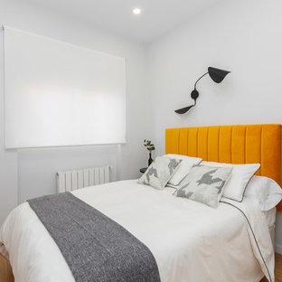 Modelo de habitación de invitados contemporánea, de tamaño medio, con paredes blancas, suelo de madera en tonos medios y suelo marrón