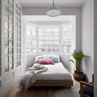 Diseño de dormitorio nórdico con paredes blancas, suelo de madera en tonos medios y suelo marrón