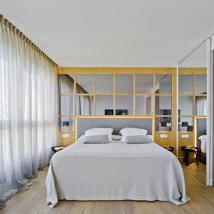 Ejemplo de dormitorio principal, actual, con paredes blancas, suelo de madera en tonos medios y suelo marrón