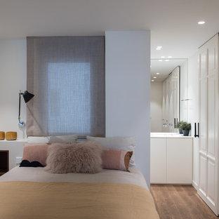 Ejemplo de dormitorio principal, contemporáneo, con paredes grises, suelo de madera en tonos medios y suelo marrón