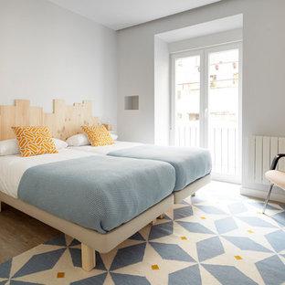 Ejemplo de dormitorio contemporáneo con suelo de madera en tonos medios, paredes grises y suelo marrón
