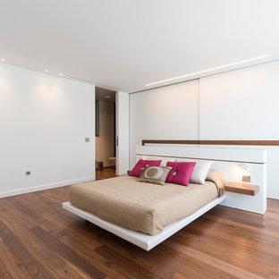 Diseño de dormitorio principal, contemporáneo, grande, con paredes blancas, suelo de madera en tonos medios y suelo marrón