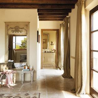 Пример оригинального дизайна: хозяйская спальня в стиле кантри с бежевыми стенами, полом из известняка и коричневым полом