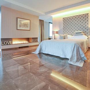 Modelo de dormitorio principal, moderno, con paredes beige, chimenea lineal y suelo beige
