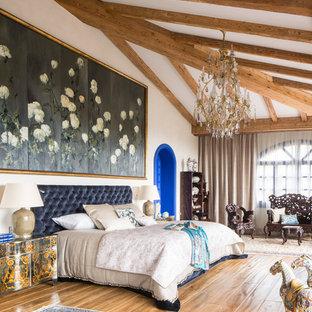 Imagen de dormitorio principal, bohemio, extra grande, sin chimenea, con paredes blancas, suelo de madera en tonos medios y suelo marrón