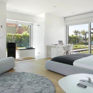 Foto de dormitorio principal, actual, grande, sin chimenea, con paredes blancas y suelo de madera en tonos medios