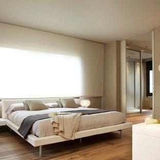 Modelo de dormitorio principal, actual, de tamaño medio, sin chimenea, con paredes beige y suelo de madera en tonos medios