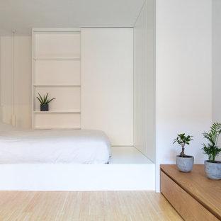 Foto de dormitorio tipo loft, nórdico, pequeño, con paredes blancas y suelo de bambú