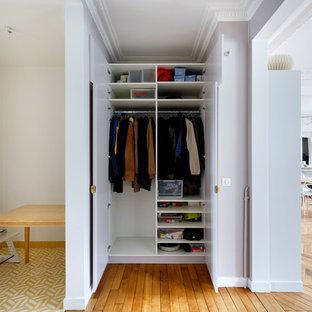 Imagen de armario unisex, contemporáneo, pequeño, con puertas de armario blancas y suelo de madera en tonos medios