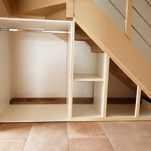 Imagen de armario vestidor unisex, moderno, pequeño, con armarios con rebordes decorativos, puertas de armario blancas y suelo de travertino