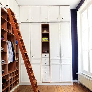 Réalisation d'un grand dressing room tradition neutre avec des portes de placard blanches et un sol en bois brun.