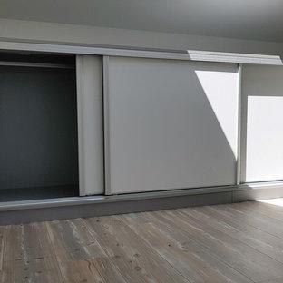 他の地域の小さい男女兼用トラディショナルスタイルのおしゃれな壁面クローゼット (リノリウムの床、茶色い床) の写真