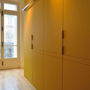 EIngebautes, Großes, Neutrales Modernes Ankleidezimmer mit Kassettenfronten, gelben Schränken und hellem Holzboden in Paris
