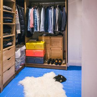 Imagen de armario de hombre, actual, de tamaño medio, con armarios abiertos, puertas de armario de madera clara, suelo de baldosas de cerámica y suelo azul