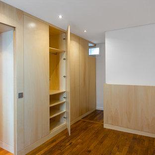 Imagen de armario unisex, actual, pequeño, con armarios con rebordes decorativos, puertas de armario de madera clara y suelo de madera en tonos medios