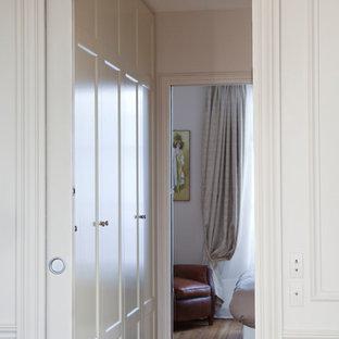 Foto de vestidor unisex, tradicional renovado, con armarios con rebordes decorativos, puertas de armario beige, suelo de madera clara y suelo marrón