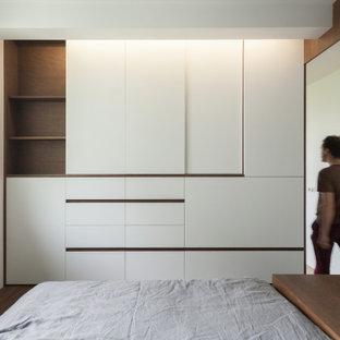 Imagen de armario y vestidor unisex, actual, pequeño, con armarios con rebordes decorativos y puertas de armario de madera en tonos medios