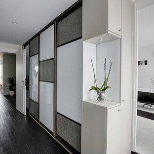 Modelo de armario vestidor unisex, contemporáneo, con armarios tipo vitrina, puertas de armario de madera en tonos medios, suelo de madera oscura y suelo negro