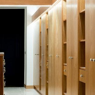Modelo de vestidor unisex, tradicional renovado, grande, con armarios con rebordes decorativos, puertas de armario rojas, suelo de baldosas de cerámica y suelo beige