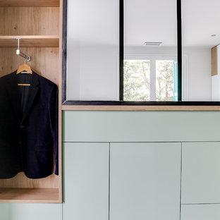 Modern inredning av ett litet walk-in-closet för könsneutrala, med öppna hyllor och gröna skåp