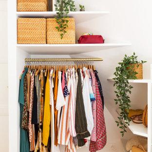 Ejemplo de armario vestidor de mujer, romántico, pequeño, con armarios abiertos, puertas de armario blancas, suelo de madera clara y suelo marrón