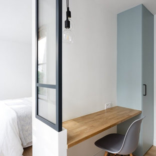 Ejemplo de vestidor unisex, escandinavo, pequeño, con armarios con paneles lisos, puertas de armario azules, suelo de madera clara y suelo beige