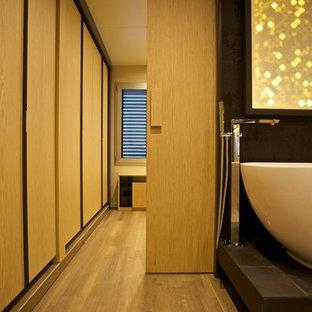 Cette image montre un grand dressing design pour un homme avec des portes de placard en bois clair et un sol en bois clair.