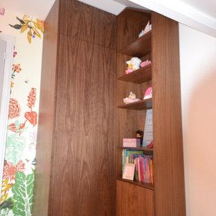 Inredning av en klassisk mellanstor garderob för kvinnor, med luckor med profilerade fronter, skåp i mörkt trä, heltäckningsmatta och grått golv
