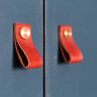 Immagine di un armadio o armadio a muro unisex minimal di medie dimensioni con ante blu, parquet chiaro, pavimento beige e ante a filo
