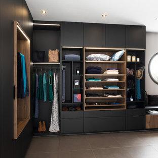 Inspiration pour un dressing design avec un placard à porte plane, des portes de placard noires et un sol marron.