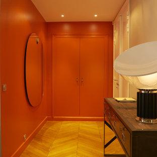 Modern inredning av ett stort walk-in-closet för könsneutrala, med orange skåp, ljust trägolv och brunt golv