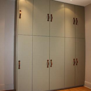 Foto de armario vestidor unisex, actual, grande, con armarios con paneles lisos, puertas de armario verdes y suelo de madera clara