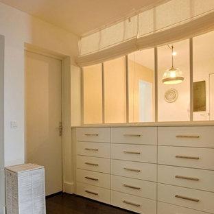 Imagen de armario vestidor unisex, actual, de tamaño medio, con armarios con rebordes decorativos, puertas de armario beige, suelo de madera oscura y suelo marrón