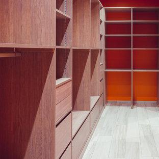 Modelo de vestidor unisex, moderno, de tamaño medio, con puertas de armario de madera clara, armarios abiertos, suelo de baldosas de cerámica y suelo blanco
