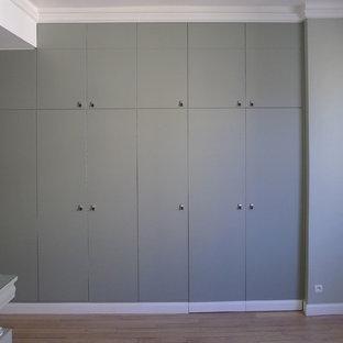 Foto de vestidor unisex, contemporáneo, de tamaño medio, con armarios con paneles lisos, puertas de armario verdes y suelo de madera clara