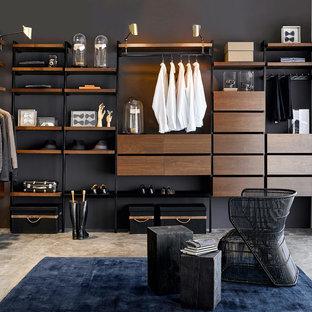 Imagen de vestidor de hombre, minimalista, grande, con puertas de armario de madera en tonos medios y suelo de cemento