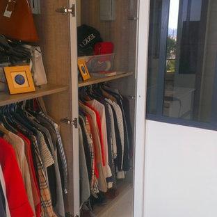 Modelo de armario de mujer, minimalista, grande, con armarios con rebordes decorativos, puertas de armario beige y suelo de baldosas de cerámica