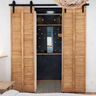 Immagine di un piccolo spazio per vestirsi unisex industriale con ante a persiana, ante in legno chiaro, parquet chiaro e pavimento beige