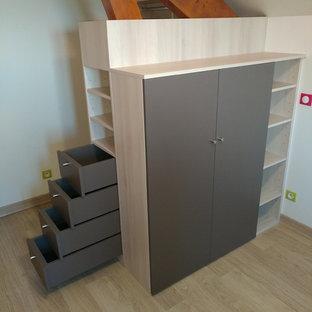 Imagen de armario vestidor unisex, pequeño, con armarios con paneles lisos, puertas de armario beige, suelo laminado y suelo gris