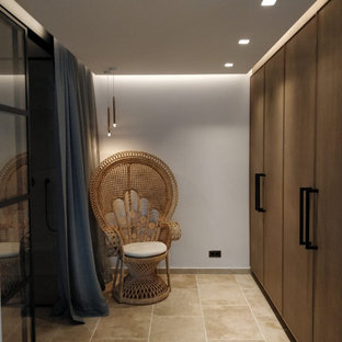 This is an example of a medium sized mediterranean dressing room for women in Other with flat-panel cabinets, medium wood cabinets, travertine flooring and beige floors.