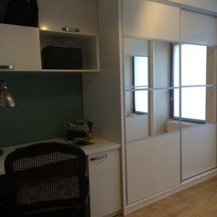 Bild på ett mellanstort funkis omklädningsrum för könsneutrala, med släta luckor, vita skåp och ljust trägolv