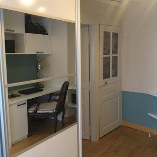 Diseño de vestidor unisex, contemporáneo, de tamaño medio, con armarios con paneles lisos, puertas de armario blancas y suelo de madera clara