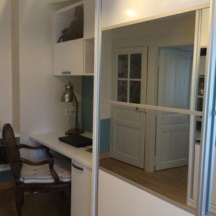 Idée de décoration pour un dressing room design de taille moyenne et neutre avec un placard à porte plane, des portes de placard blanches, un sol en bois clair et un plafond en poutres apparentes.