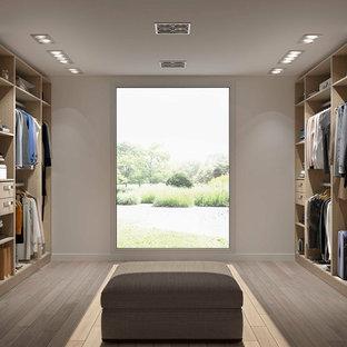 Imagen de vestidor unisex, escandinavo, grande, con puertas de armario de madera clara, armarios abiertos y suelo de madera clara