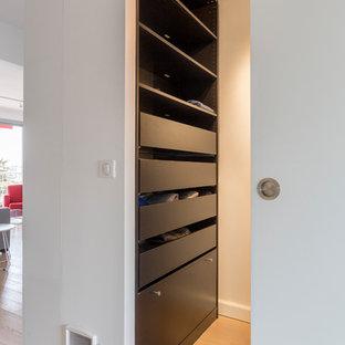 Foto di un piccolo spazio per vestirsi unisex design con nessun'anta, ante nere, parquet chiaro e pavimento beige