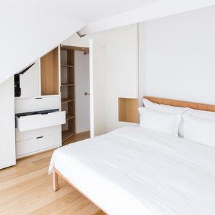 Modelo de armario unisex, contemporáneo, grande, con armarios con rebordes decorativos, puertas de armario blancas, suelo de madera clara y suelo beige