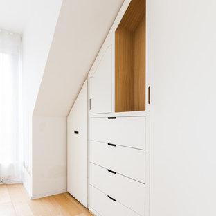 Ejemplo de armario unisex, actual, grande, con armarios con rebordes decorativos, puertas de armario blancas, suelo de madera clara y suelo beige