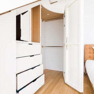 EIngebautes, Großes, Neutrales Modernes Ankleidezimmer mit Kassettenfronten, weißen Schränken, hellem Holzboden und beigem Boden in Paris