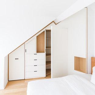 Imagen de armario unisex, contemporáneo, grande, con armarios con rebordes decorativos, puertas de armario blancas, suelo de madera clara y suelo beige